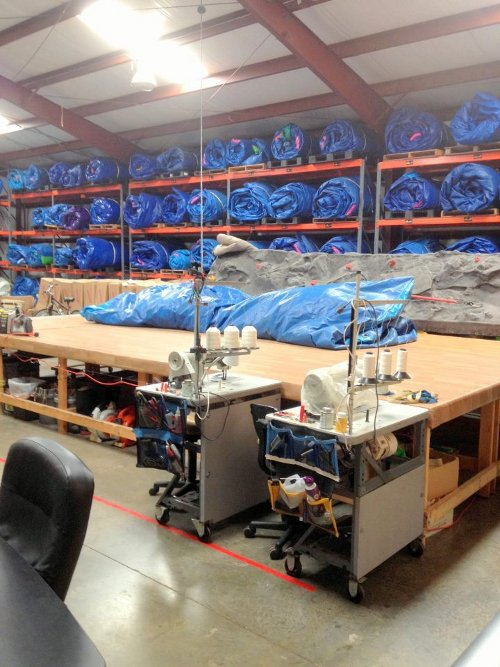 warehouse with rolled up inflatable material stacked on shelves, repair work stations, and sewing machines